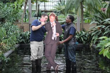 Garfield Park Conservatory staffers hang a life-size photo of visionary Chicago Park District Cultural and Natural Resources Director Adam Schwerner above a pond before his going-away gala. Schwerner got hired by Disney to take over as the California theme park's horticulture chief.
