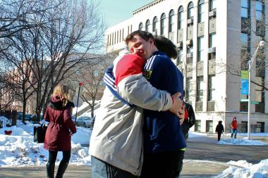 David Melia (r.) hugs his friend Ben Rios in front of the DePaul University Student Center.