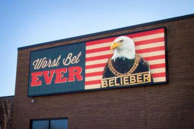 "A new electronic billboard message reading ""Worst Bet EVER"" with an American eagle featuring a ""BELIEBER"" chain."