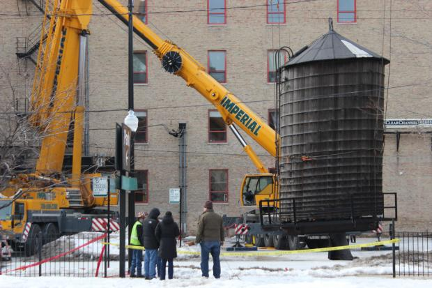 "Crews safely took down a leaning River North water tower Saturday afternoon a day after it sent down "" torrential downpour "" on the building it sits atop at 409 W. Huron St."