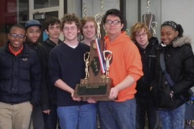 The state's top high school chess player will start college as a five-time national champion. The Whitney Young High School chess team won a second consecutive state championship Saturday. Sam Schmakel, left, helps hold the trophy.