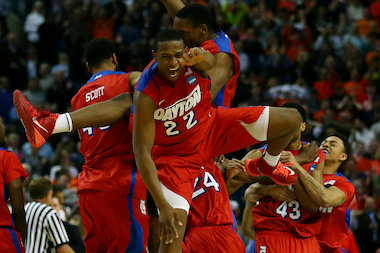 The Dayton Flyers, including Simeon Career Academy graduate Kendall Pollard (22), celebrate after defeating the Ohio State Buckeyes 60-59 in the second round of the 2014 NCAA Men's Basketball Tournament at the First Niagara Center on March 20, 2014, in Buffalo.