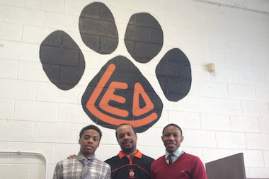 Leo High School boys basketball coach Noah Cannon is sandwiched by sophomore guards Kewan Smith (l.) and Darius Branch, who have helped lead the Lions to Friday's IHSA Class 2A sectional title game.