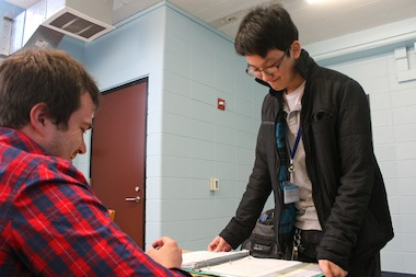 Volunteer Chris Dierks works with freshman student Patrick Liao in the Colleen Henry Writing Center at Lincoln Park High School.