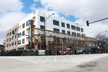 The four-story apartment building with ground-level storefronts should open this summer, a university official said.