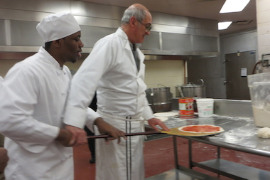 Chef Bruno Abate helps a student maneuver a pizza peel.