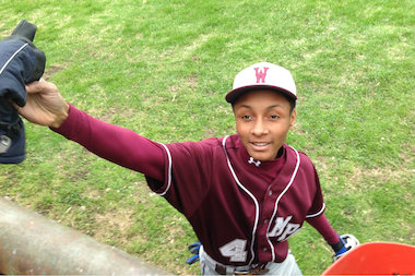 The Dowling family has lived just beyond the right field fence of Morgan Park Academy's baseball field for the last 24 years. Here, Morgan Park right fielder Brandon Miller returns a glove that dropped into play during a game against the Chicago High School for Agricultural Sciences.