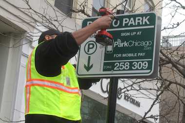 A worker for LAZ Parking installs a new ParkChicago sign near a West Loop parking meter on Madison Street.
