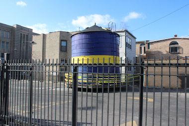 The water tower tank sits in a parking lot near the Swedish American Museum.