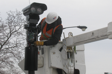 A Xerox contractor installs a new red light camera at the corner of Clark Street and Irving Park Road.