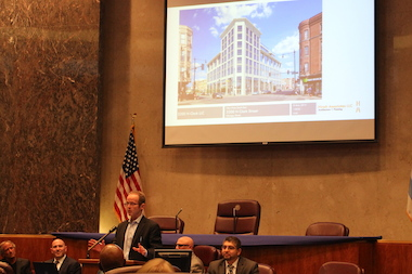 Ald. Tom Tunney speaks in front of an artist's rendering of the proposed 3200 N. Clark St. building at Thursday's Plan Commission meeting.