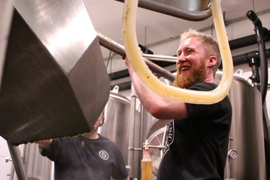 "Ben Saller of Atlas Brewing Company shovels spent mash while brewing ""Saphir and Loathing."""