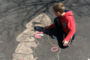 Megan Doherty Jamen and Pat Jamen's 8-year-old son, Colin, works on drawing a Blackhawks logo with chalk on Saturday. Game 3 of the Hawks' series against the Wild is Tuesday at 8 p.m. in Minnesota.