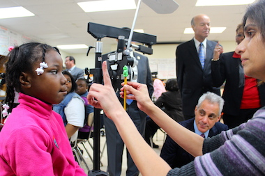 Mayor Rahm Emanuel watches a student get an eye exam at Sumner Elementary.