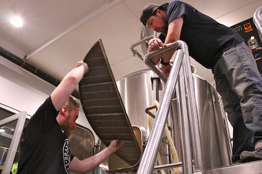 Nate Albrecht, top, of Aleman Brewing, looks on as Ben Saller cleans a tank at Atlas Brewing.