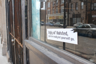 The stickers have been applied to empty storefronts up and down Halsted Street.