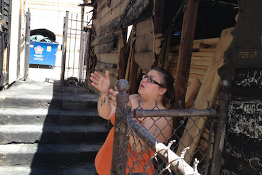 Chloe Pineda, a sister of one of the tenants displaced by a fire in Bridgeport, shows off some of the damage.
