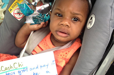TIna Gaddy's daughter holds the blue spinner that had $60 attached to it from Hidden Cash Chicago.