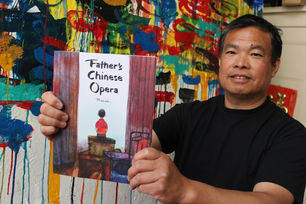 "Artist Rich Lo displays a copy of ""Father's Chinese Opera,"" the first book where he serves as author and illustator."