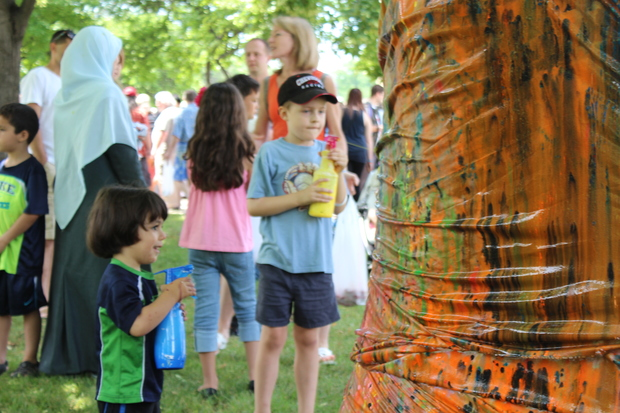 Budding artists use spray bottles to decorate a sheet tied around a tree at Jefferson Memorial Park as part of the celebration of the opening of the Ed Paschke Art Center. The artwork will hang in the center.