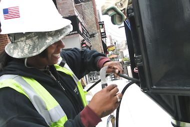 Electrician Monique Rhivers works Thursday morning on installing a new traffic light at the Milwaukee and Wood intersection.