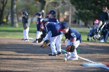 Young ballplayers field ground balls at the Oz Park Baseball Association opening day celebration.