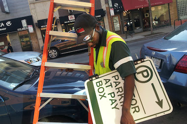 A worker takes down an old parking meter sign so new ones can be installed for ParkChicago, a new pay-by-phone app.