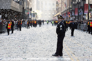 A Chicago police officer stands in a sea of ticker tape after the White Sox World Series parade on Oct. 28, 2005.