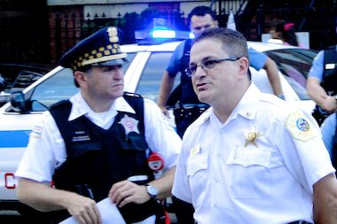 Former Shakespeare District Cmdr. Frank Valadez (right) at an outdoor community policing meeting