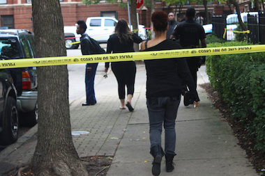 Residents cross police crime scene tape near the building where a 19-year-old man was shot dead Sept. 11.