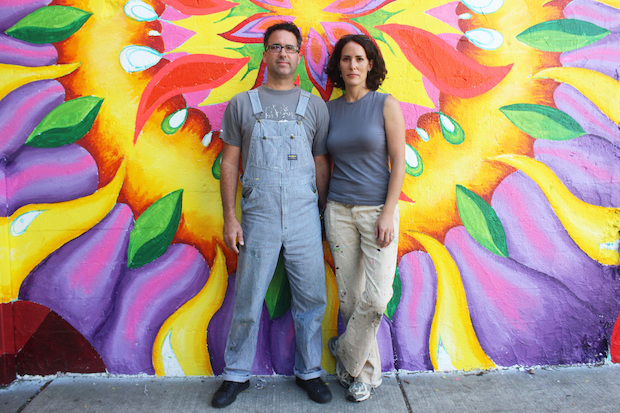Lea Pinsky and Dustin Harris are painting the mural under the Metra viaduct.
