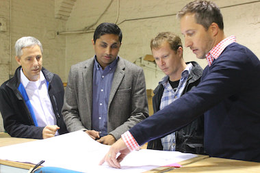 Investor David Brown, Ald. Ameya Pawar and Band of Bohemia owners Michael Carroll and Craig Sindelar look over blueprints for the culinary brewhouse, set to open in 2015.
