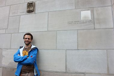 Fossil tour guide Asa Kaplan poses outside Tribune Tower, whose building blocks are millions of years old.