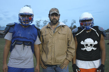 Curie assistant coach Doug Bartlett, who was a defensive end for the Philadelphia Eagles, is shown with two of his players, Angel Magna (l.) and Jamie Salis. Curie faces New Trier on Saturday in an IHSA Class 8A second-round playoff game in Winnetka.
