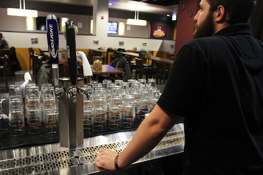 Bartender Matthew McLaughlin, 22, awaits customers at Ireland's, Loyola University's first-ever bar.