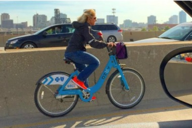 A woman rides a Divvy rental southbound on the Dan Ryan Expressway.