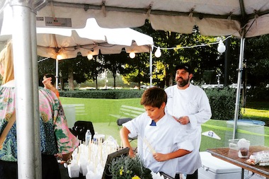 Jack Lembeck works with chef Michael Taus during a Trotter Project fundraiser near Buckingham Fountain in September.
