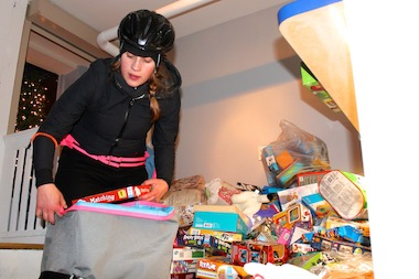 Kelsey Phillips, 24, a Downtown bike messenger, unpacks toys at the Shurpa headquarters of Toys for Tots.
