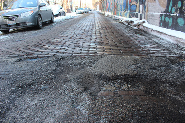 Potholes mar Glenwood Avenue as business owners await the cobblestone restoration.