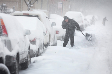 A man digs out his car along a snow-covered street on February 1, 2015