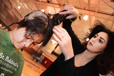 Malak Elshafei, a student with Mario Tricoci School, shaves the head of St. Xavier student Mallorie Rosales. Rosales had more than 20 inches of hair shaved.