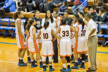 Whitney Young girls basketball coach Corry Irvin is surrounded by her players during a team huddle.