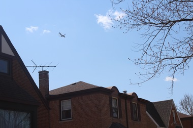 A plane headed to O'Hare Airport soars over homes in Edison Park.