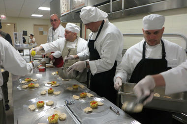 Inmates at Cook County Jail prepare a meal under the direction of chef Bruno Abate (at rear).
