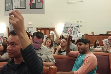 Residents hold up anti-gentrification flyers at the 53rd Annual Congress of the Logan Square Neighborhood Association.
