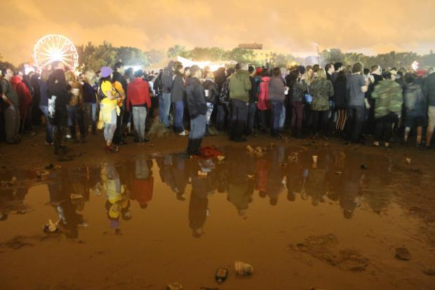 A crowd watches the stage during Riot Fest 2013, near a puddle of mud in Humboldt Park.