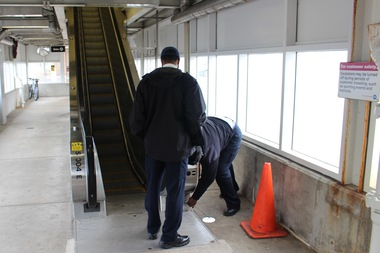 CTA workers try to get the elevator started at the Green Line stop at 35th Street — no luck.