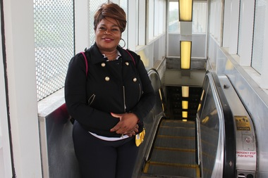 Darlene Amao next to the inoperational escalator at the Green Line's 35th Street station: