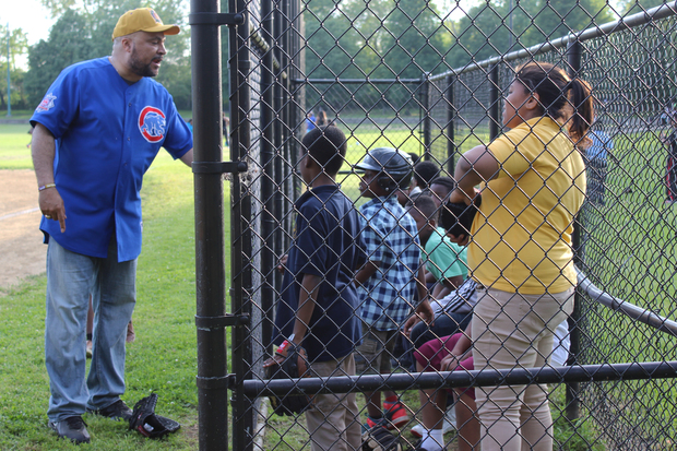 A volunteer coach talks to players as part of the Englewood Police/Youth Baseball League in 2015.