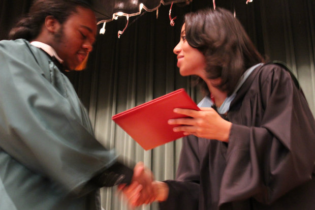 Fenger High School principal Liz Dozier hands a diploma to a student at her last graduation before leaving the Chicago Public School system.